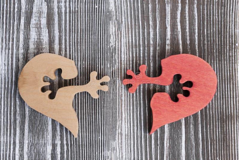 Dos medios corazones con las manos en el fondo imagenes de archivo