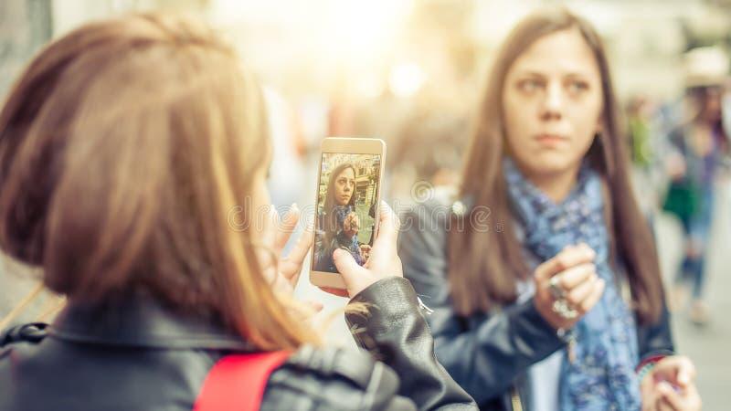 Dos medios sociales de observación felices de Internet de las amigas en smartph foto de archivo libre de regalías