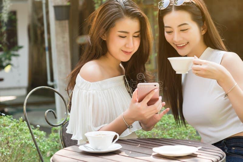 Dos medios sociales del uso independiente hermoso de la mujer en smartphone adentro fotografía de archivo libre de regalías