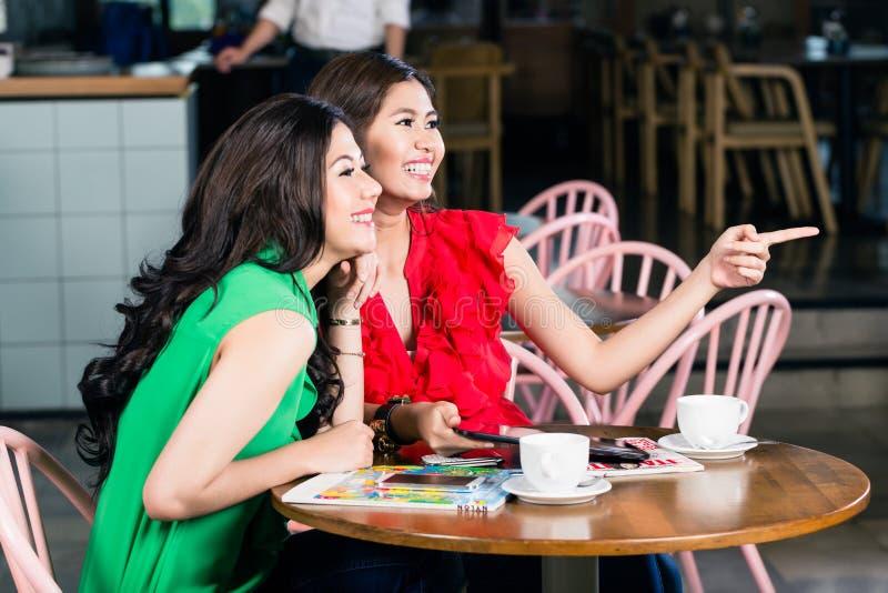 Dos mejores amigos que hablan mientras que bebe junto una taza de café fotografía de archivo libre de regalías