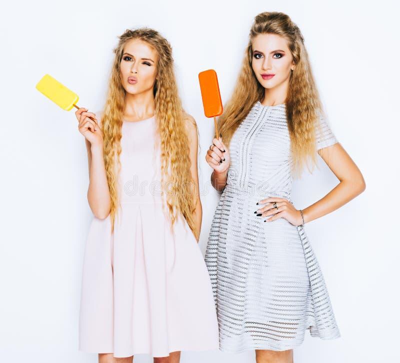 Dos mejores amigos que tienen helado junto interior en fondo amarillo Ciérrese para arriba de las mujeres jovenes que comen el he imagenes de archivo