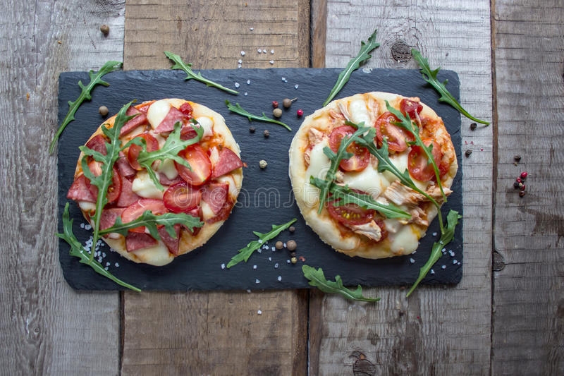Dos mini pizzas y arugula fresco imagen de archivo