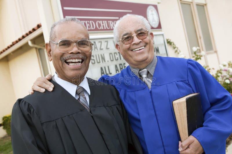 Dos ministros delante del retrato de la iglesia foto de archivo libre de regalías