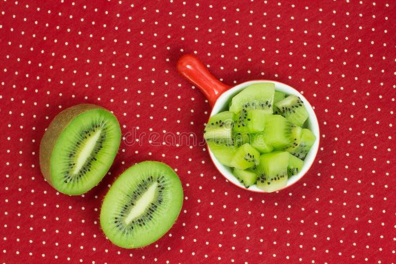 Dos mitades de la fruta de kiwi El kiwi cortó en pedazos en una placa roja imagen de archivo