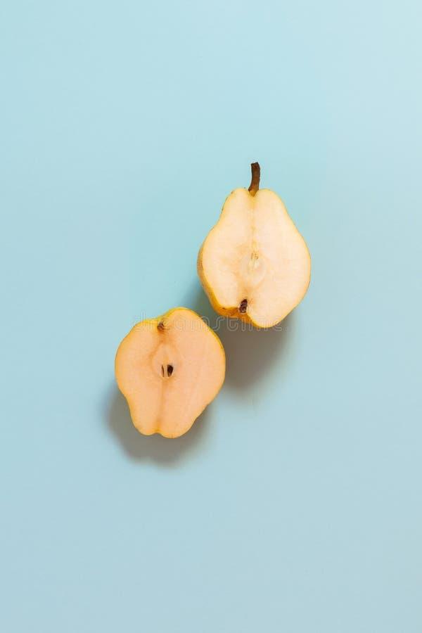 Dos mitades de un corte amarillean la pera en un fondo azul en colores pastel fotografía de archivo libre de regalías