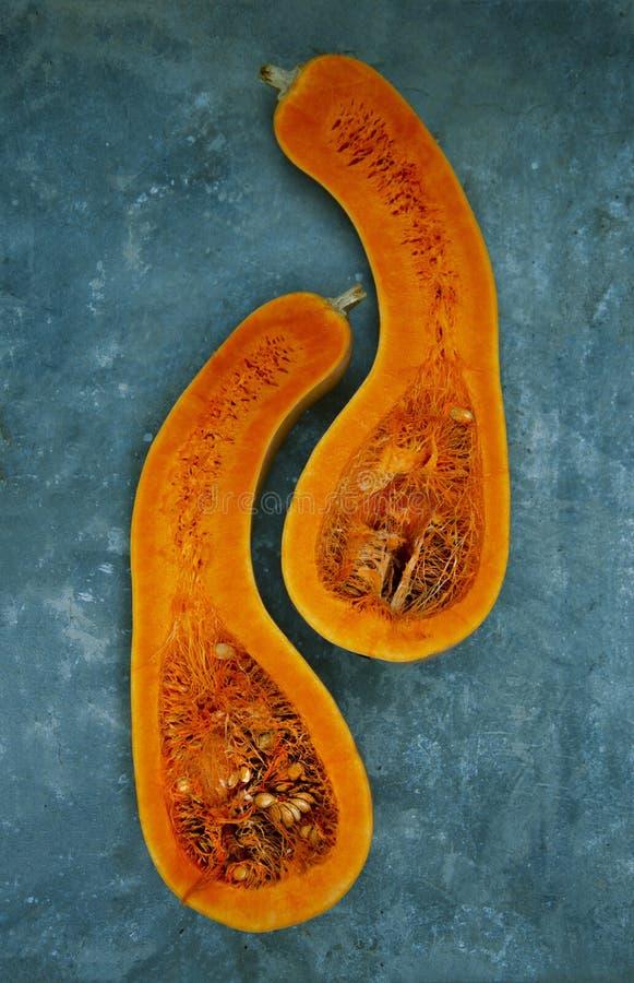 Dos mitades de una calabaza en forma de pera del color anaranjado están situadas verticalmente contra color de la turquesa fotografía de archivo libre de regalías