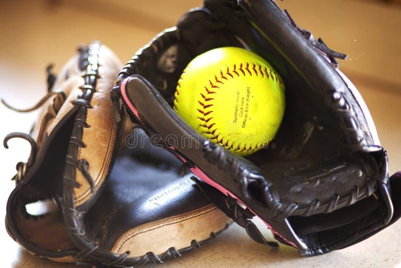 Dos mitones del softball y un softball amarillo foto de archivo