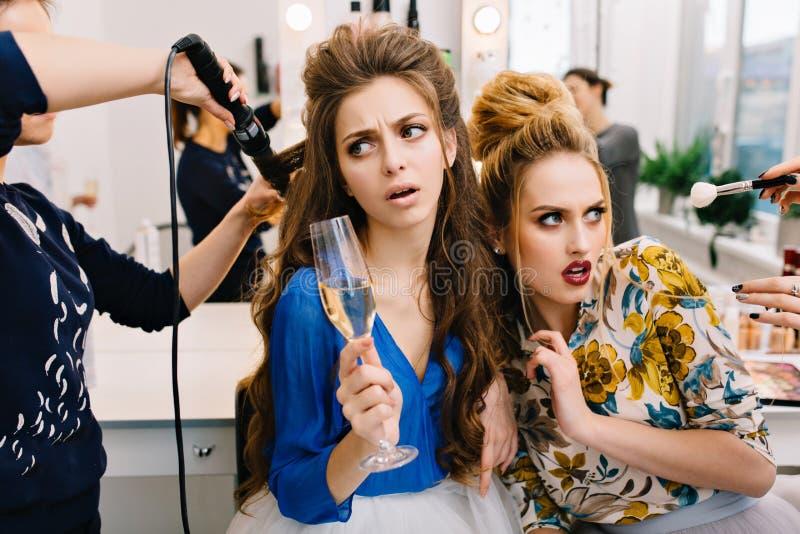 Dos modelos asombrosos elegantes en sal?n de belleza durante la preparaci?n a ir de fiesta Tocado de moda, servicio del peluquero fotos de archivo
