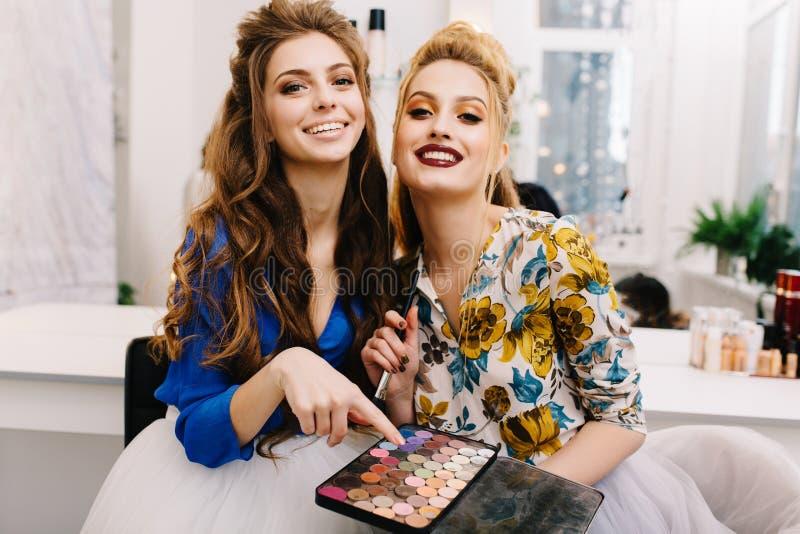 Dos modelos atractivos de moda con el maquillaje elegante, tocado de lujo que se divierte junto en sal?n del haidresser fotografía de archivo