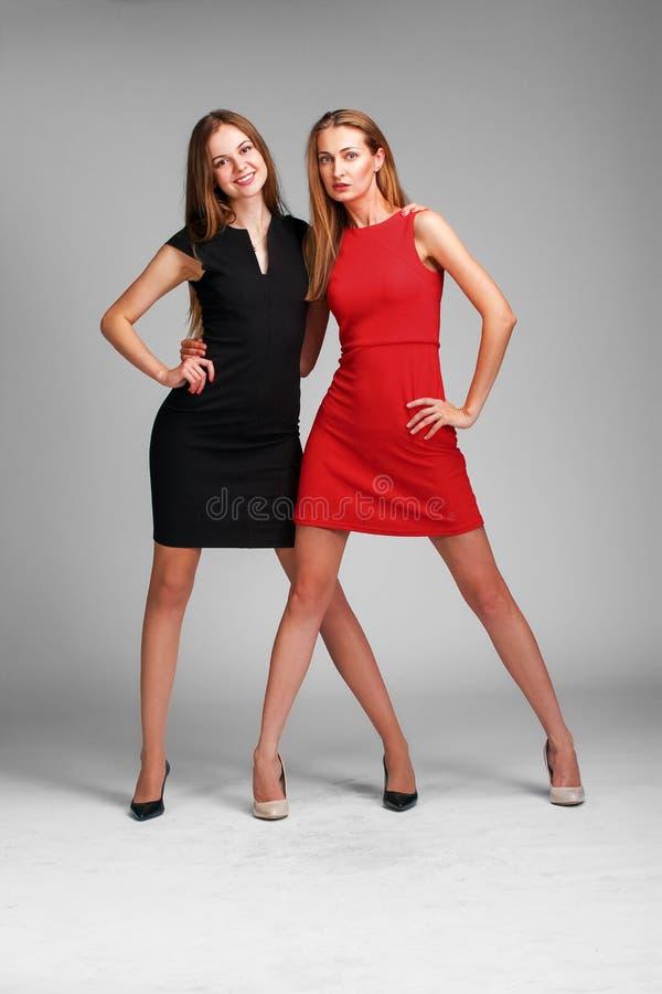 Dos modelos de moda caucásicos que presentan en stusio en backgroun gris fotografía de archivo libre de regalías