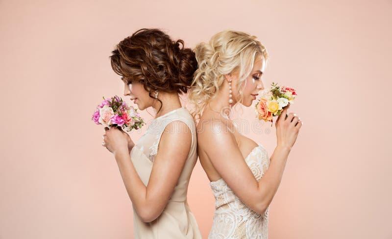 Dos modelos de moda con el retrato de la belleza del ramo de las flores, estudio hermoso de las mujeres tirado en beige imagen de archivo libre de regalías