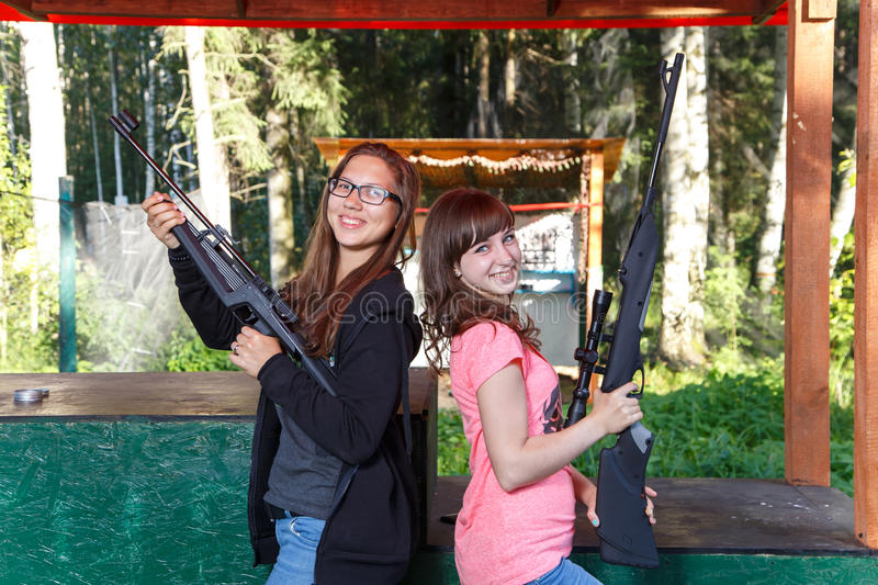 Dos modelos femeninos hermosos que presentan con los armas en radio de tiro fotografía de archivo