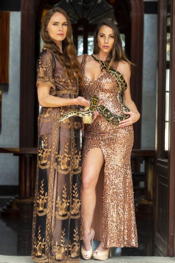 Dos modelos morenos hispánicos hermosos presentan con una serpiente del constrictor de boa alrededor de su cuerpo fotografía de archivo