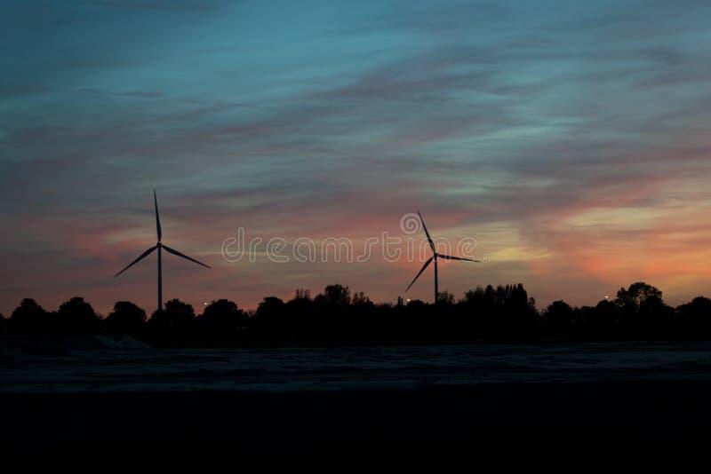 Dos molinoes de viento modernos silueteados contra el cielo de igualación imagenes de archivo
