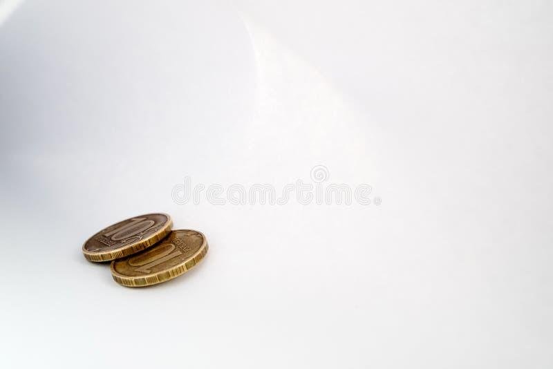 Dos monedas de cobre que mienten en una hoja de la sombra ligera del Libro Blanco y luz alrededor del perímetro fotografía de archivo libre de regalías
