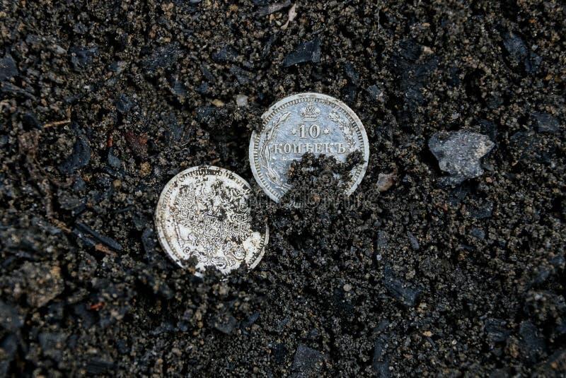 Dos monedas de plata viejas blancas que mienten en tierra negra fotografía de archivo libre de regalías