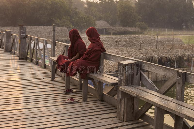 Dos monjes birmanos que asientan en el puente de U Bein imagen de archivo libre de regalías