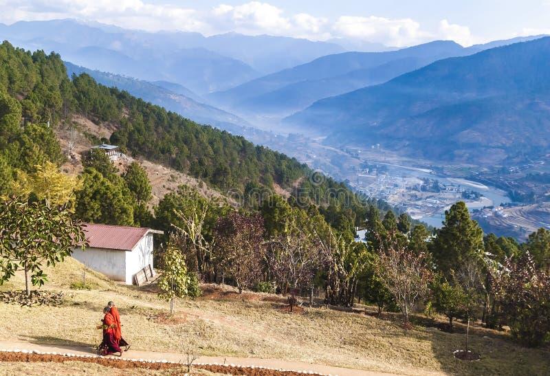 Dos monjes budistas en su ropa roja tradicional en el territorio del monasterio budista de las mujeres en Bhután, valle de Punakh imagen de archivo libre de regalías