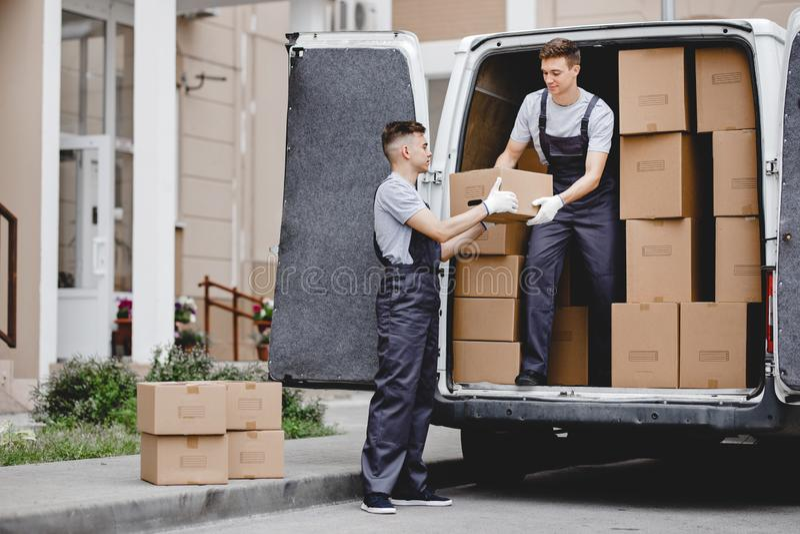 Dos motores hermosos jovenes que llevan los uniformes están descargando la furgoneta por completo de cajas Movimiento de la casa, fotografía de archivo