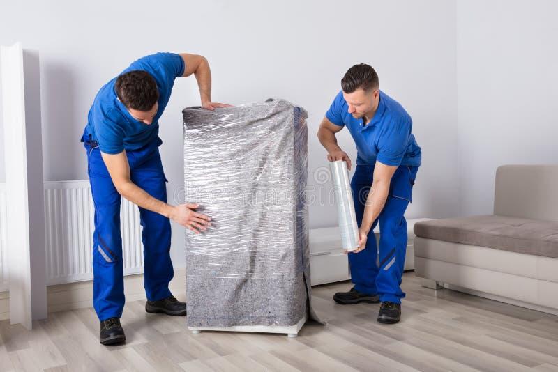 Dos motores masculinos que embalan los muebles imágenes de archivo libres de regalías
