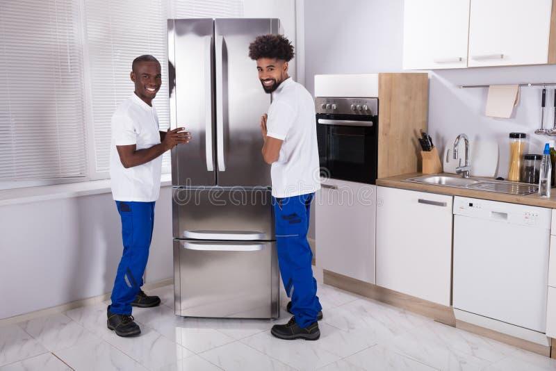 Dos motores masculinos que fijan el congelador en la cocina foto de archivo libre de regalías