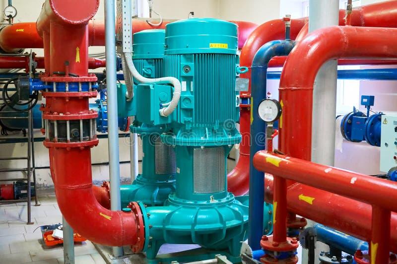 Dos motores verticales pintaron azul con las bombas conectadas con los tubos pintaron rojo fotos de archivo