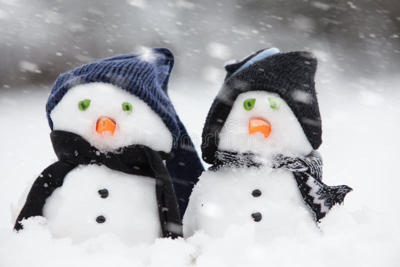 Dos muñecos de nieve lindos vestidos para el invierno imagen de archivo