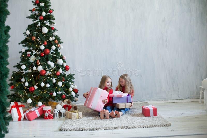 Dos muchachas abren luces de la guirnalda del árbol de navidad del Año Nuevo de los regalos de Navidad foto de archivo libre de regalías