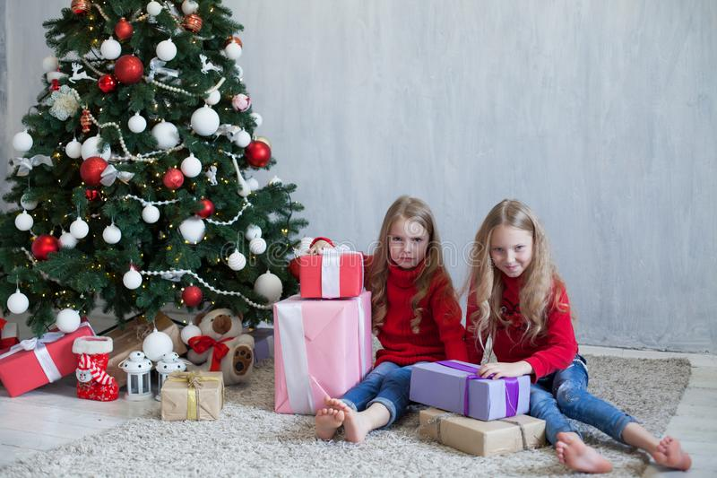 Dos muchachas abren luces de la guirnalda del árbol de navidad del Año Nuevo de los regalos de Navidad imagenes de archivo