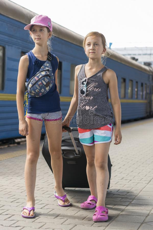 Dos muchachas adolescentes en la estación de tren con una maleta Dos hermanas están tirando de una maleta negra grande y pesada c imagen de archivo libre de regalías