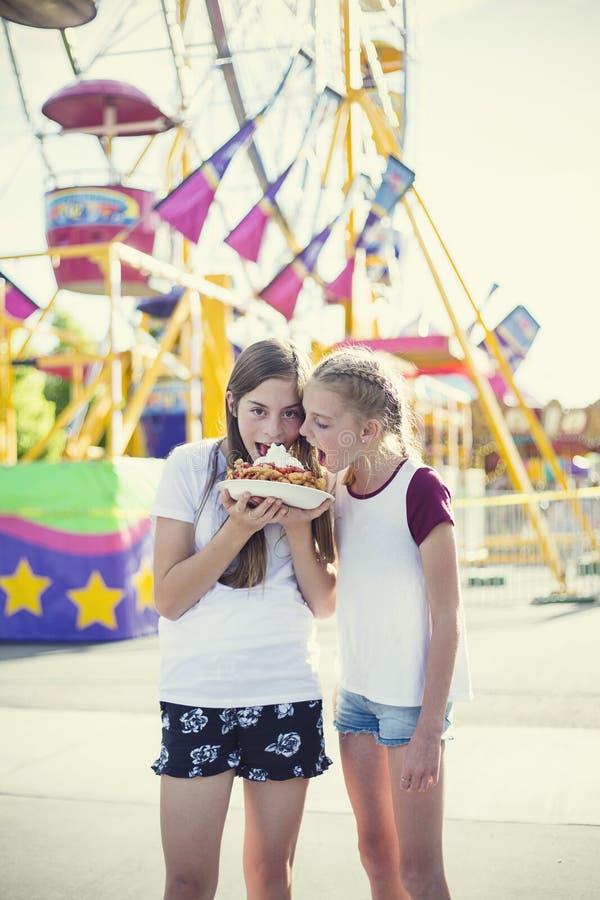 Dos muchachas adolescentes que hacen una cara tonta mientras que come una torta del embudo en un paseo del parque de atracciones foto de archivo