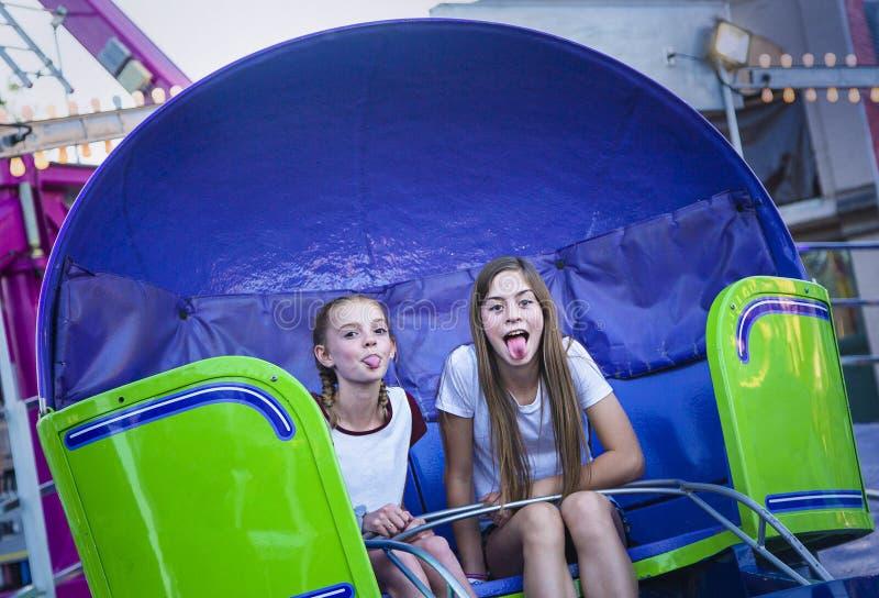 Dos muchachas adolescentes que hacen una cara tonta mientras que monta un paseo del parque de atracciones imagen de archivo libre de regalías