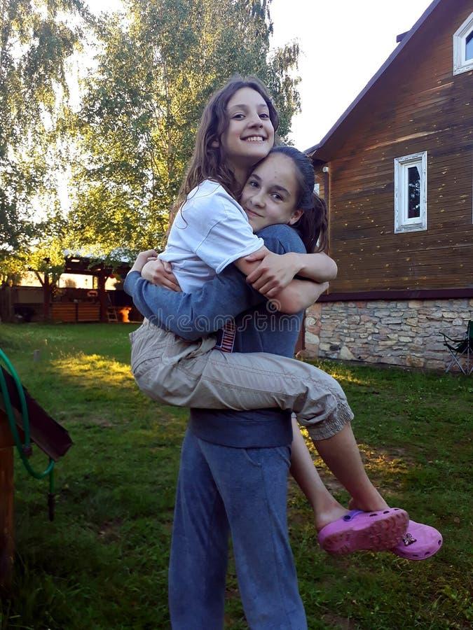 Dos muchachas adolescentes que juegan y que se abrazan fotografía de archivo libre de regalías