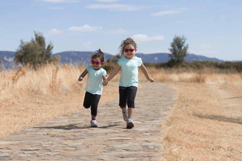 Dos muchachas alegres que corren abajo del camino foto de archivo libre de regalías