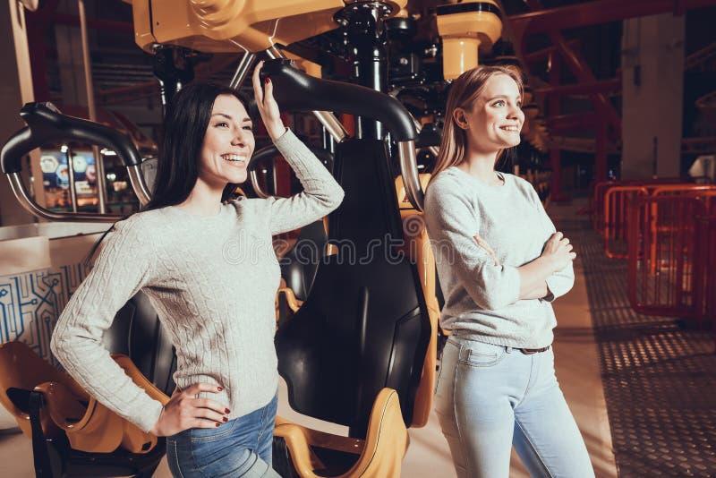 Dos muchachas alegres que se divierten en el parque de atracciones fotografía de archivo