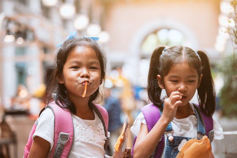 Dos muchachas asiáticas lindas del niño con la mochila que comen la crepe junto después de escuela fotos de archivo libres de regalías