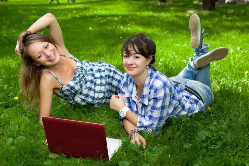 Dos muchachas atractivas con una computadora portátil en el parque imagen de archivo libre de regalías