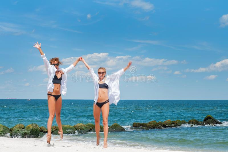 Dos muchachas atractivas en los bikinis que saltan en la playa Mejores amigos que se divierten fotos de archivo