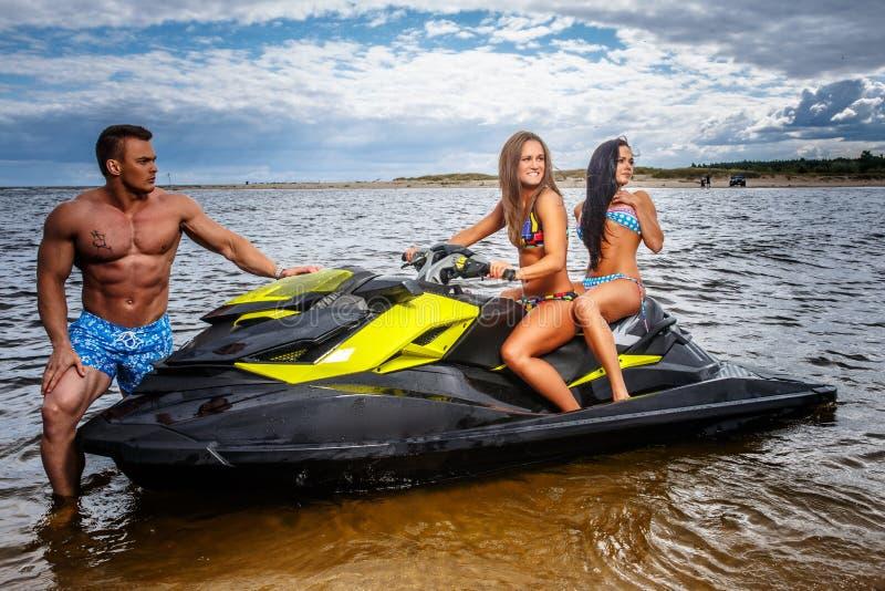 Dos muchachas atractivas en traje de baño y varón muscular descamisado, se divierten con un esquí del jet en un mar imagen de archivo