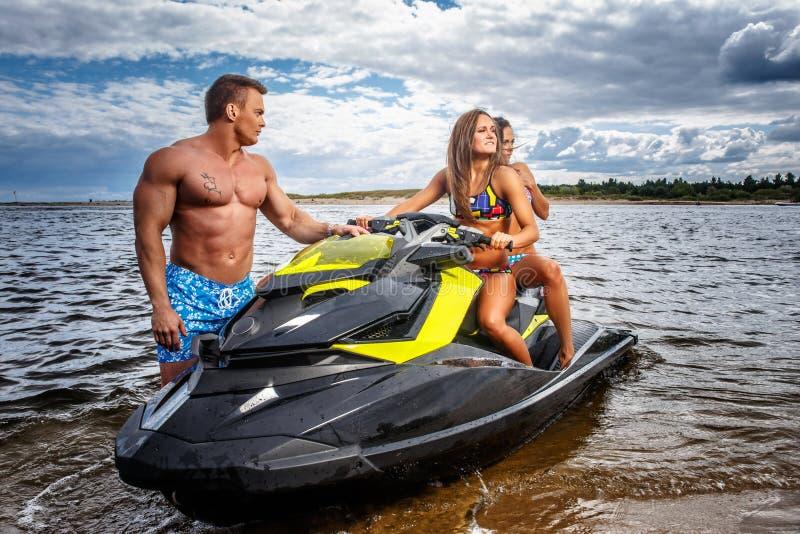 Dos muchachas atractivas en traje de baño y varón muscular descamisado, se divierten con un esquí del jet en un mar fotografía de archivo