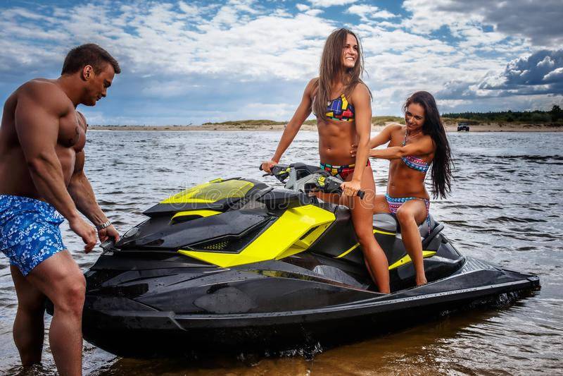 Dos muchachas atractivas en traje de baño y varón muscular descamisado, se divierten con un esquí del jet en un mar foto de archivo libre de regalías