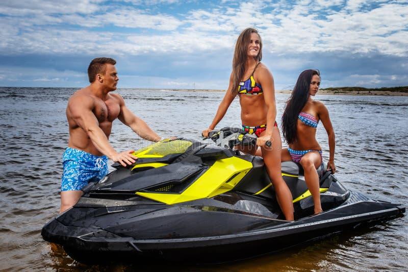 Dos muchachas atractivas en traje de baño y varón muscular descamisado, se divierten con un esquí del jet en un mar imagenes de archivo