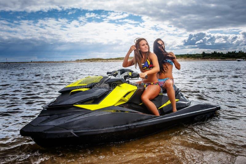 Dos muchachas atractivas en un traje de baño, sentándose en un esquí del jet, se divierten en un ocio fotos de archivo