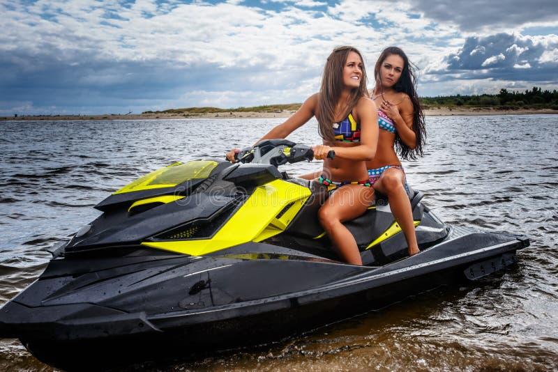 Dos muchachas atractivas en un traje de baño, sentándose en un esquí del jet, se divierten en un ocio foto de archivo libre de regalías