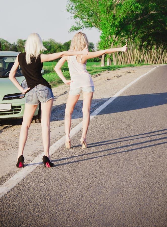 Dos muchachas atractivas que colocan el coche cercano y que hacen autostop fotos de archivo