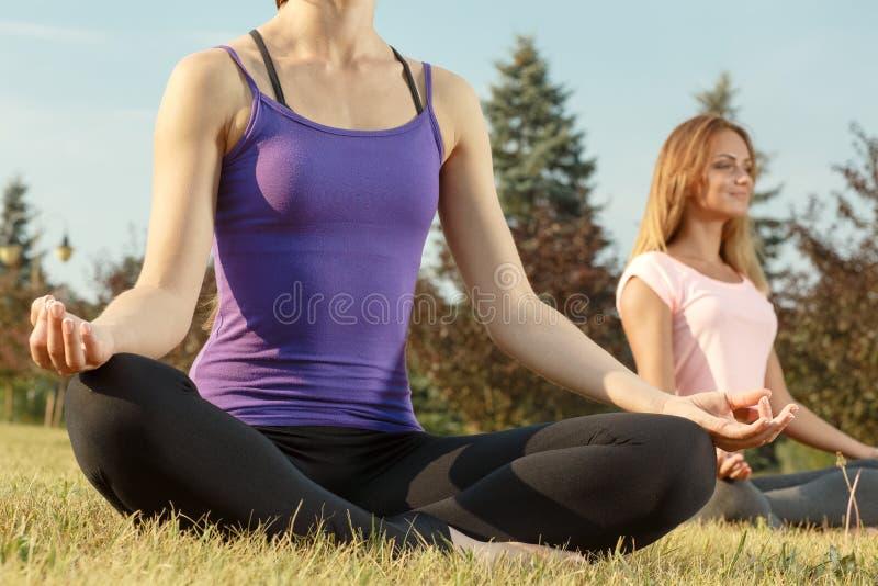 Dos muchachas atractivas que hacen yoga fotos de archivo