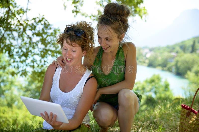Dos muchachas bonitas en la hierba con una tableta digital fotografía de archivo libre de regalías