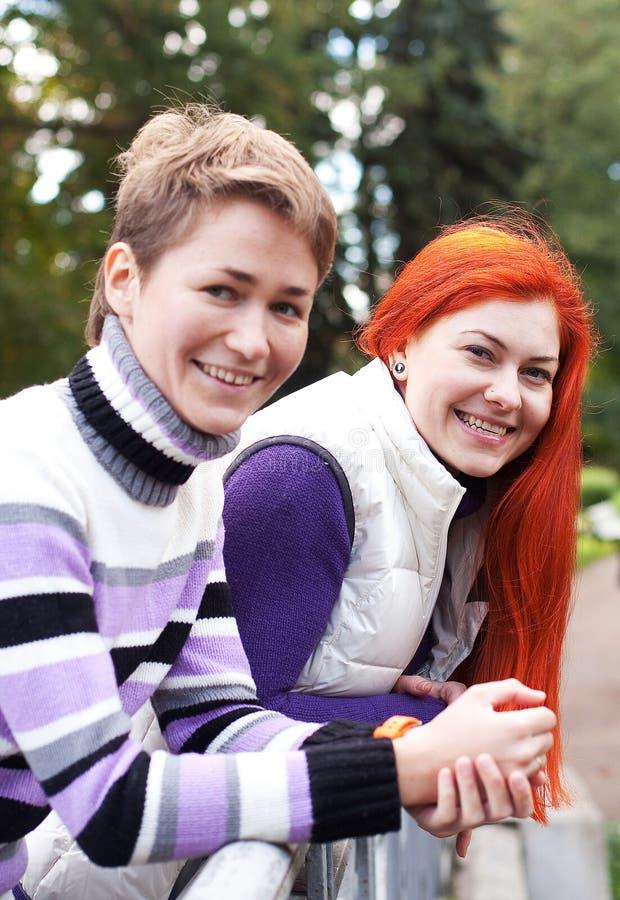 Dos muchachas bonitas que caminan en parque del otoño imagen de archivo