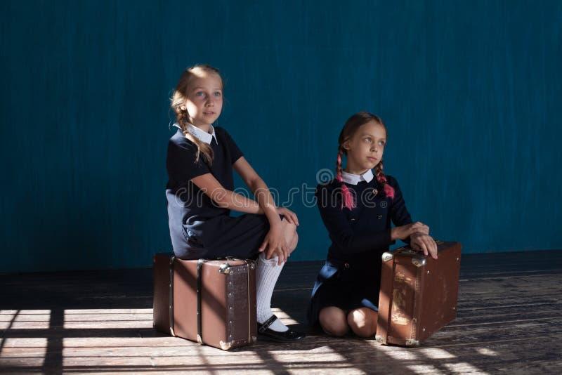 Dos muchachas con las maletas retras imagen de archivo