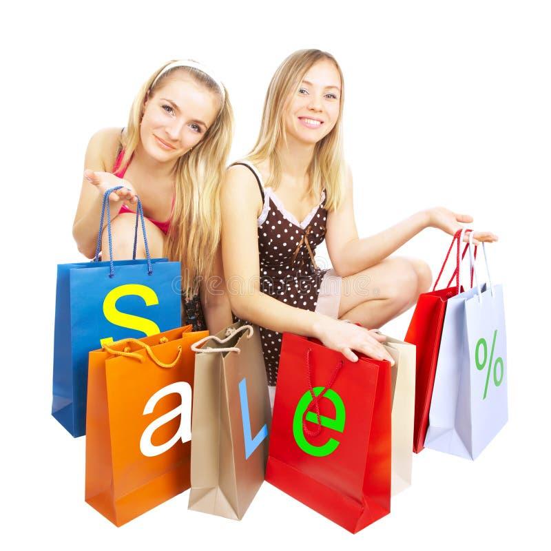 Dos muchachas con los bolsos - compras de la comparación. ¡Venta! fotos de archivo